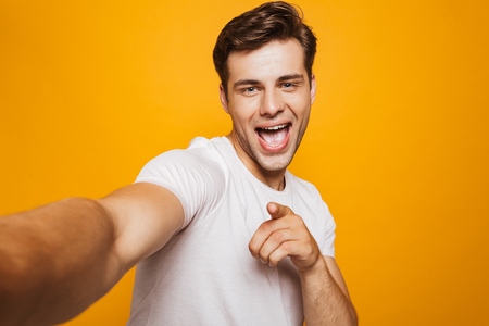 Portrait of a happy young man taking a selfie with outsretched hand, pointing finger isolated over yellow background