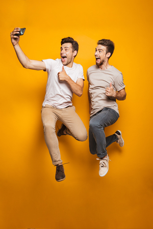 Full length portrait of a two excited young men best friends taking a selfie while jumping isolated over yellow background