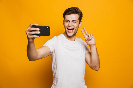 Portrait of a happy young man taking a selfie isolated over yellow background