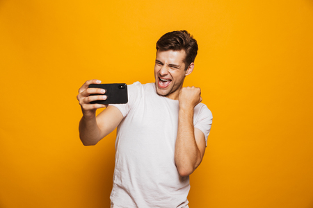 Portrait of a happy young man taking a selfie isolated over yellow background, celebrating success