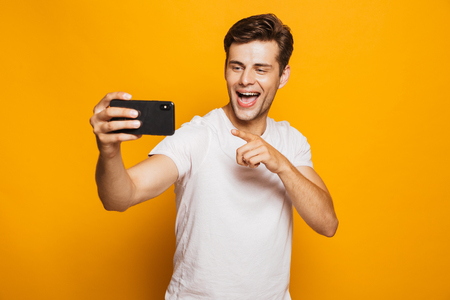 Portrait of a cheerful young man taking a selfie isolated over yellow background, pointing finger
