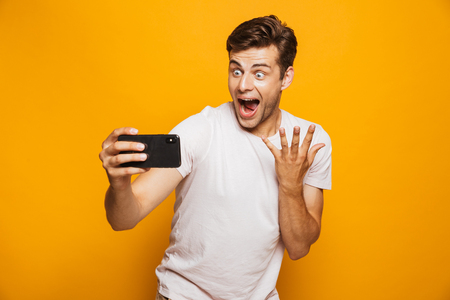 Portrait of a joyful young man taking a selfie isolated over yellow background, celebrating success Stock Photo