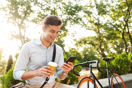 Portrait of a smiling young man dressed in shirt using mobile while sitting with cup of coffee and bicycle outdoors