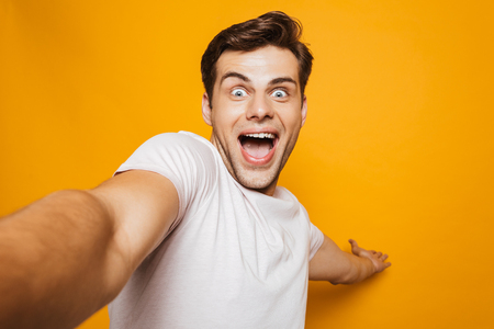 Portrait of an excited young man taking a selfie with outsretched hand isolated over yellow background