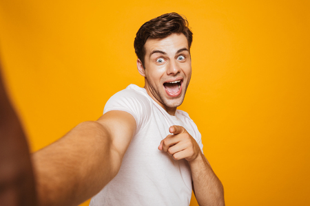 Portrait of a cheerful young man taking a selfie with outsretched hand, pointing finger isolated over yellow background