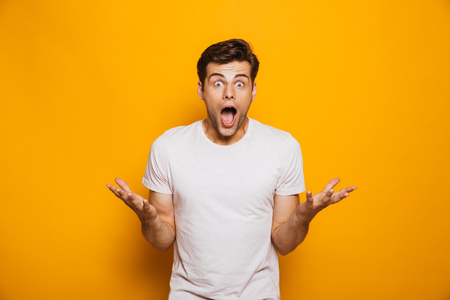 Portrait of a thrilled young man celebrating success isolated over yellow background Stok Fotoğraf