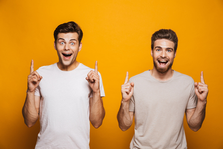 Portrait of a two cheerful young men best friends pointing fingers up at copy space isolated over yellow background Imagens