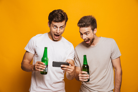 Portrait of a two happy young men best friends looking at mobile phone while holding beer bottles and shouting isolated over yellow background Standard-Bild