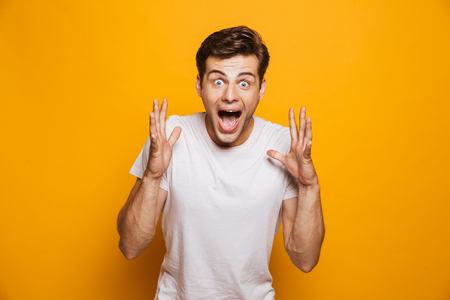 Portrait of an excited young man celebrating success isolated over yellow background