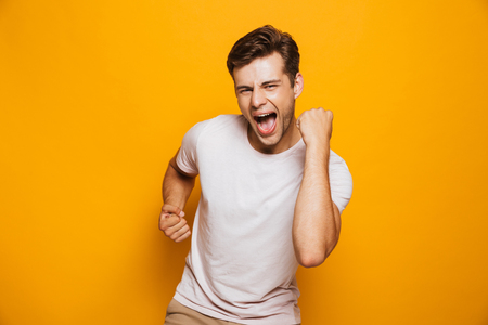 Portrait of a cheerful young man celebrating success isolated over yellow background