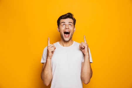 Portrait of a happy young man pointing fingers up at copy space isolated over yellow background
