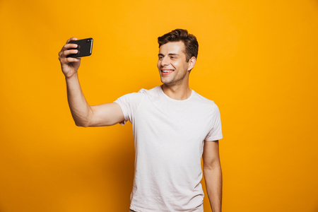 Portrait of a cheerful young man taking a selfie isolated over yellow background Stock Photo