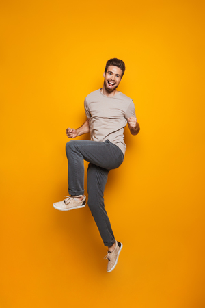 Full length portrait of a cheerful young man jumping and celebrating success isolated over yellow background Reklamní fotografie