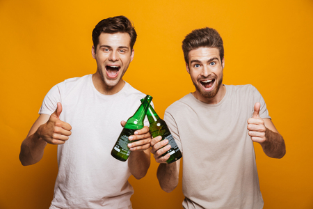 Portrait of a two happy young men best friends toasting with beer bottles showing thumbs up isolated over yellow background Фото со стока