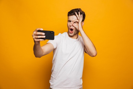 Portrait of a cheerful young man taking a selfie isolated over yellow background, showing ok