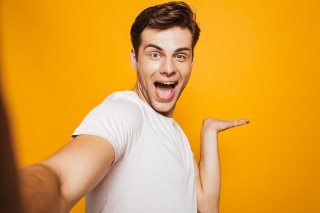 Portrait of a happy young man taking a selfie with outsretched hand isolated over yellow background