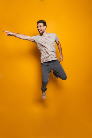 Full length portrait of a happy young man jumping and pointing away isolated over yellow background Reklamní fotografie