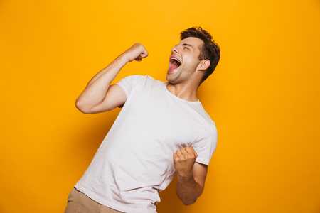 Portrait of a joyful young man celebrating success isolated over yellow background Reklamní fotografie