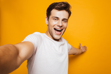 Portrait of a cheerful young man taking a selfie with outsretched hand isolated over yellow background