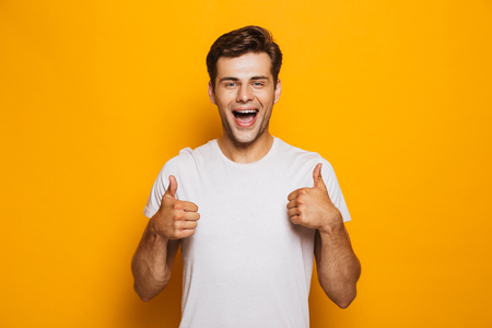 Portrait of a happy young man showing thumbs up gesture isolated over yellow background