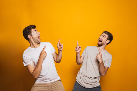 Portrait of a two happy young men best friends pointing fingers up at copy space isolated over yellow background Imagens