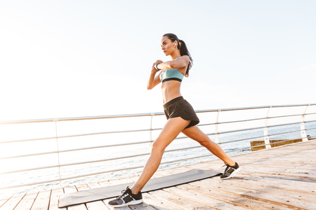 Image of strong sporty woman 20s in tracksuit doing exercises and stretching body on boardwalk near seaside with wireless earbud