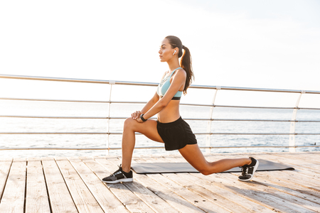 Profile photo of brunette fitness woman 20s in tracksuit doing lunges and stretching legs on boardwalk near seaside