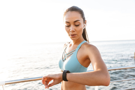 Image closeup of feminine caucasian woman 20s in sportswear looking at wrist watch while warming up and doing sports on boardwalk in sunny morning