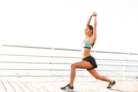 Sportive photo of brunette fitness sportswoman 20s in tracksuit stretching legs and raising arms during workout on boardwalk at seaside Stock Photo