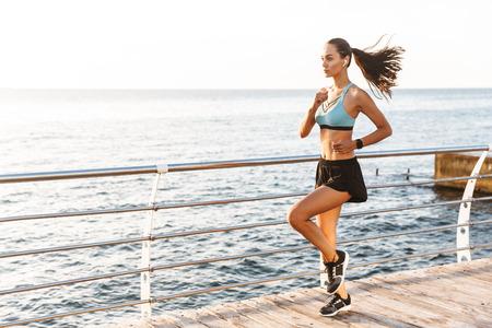 Photo of beautiful athletic sportswoman 20s in sportswear running along boardwalk near seaside in morning with wireless earbud