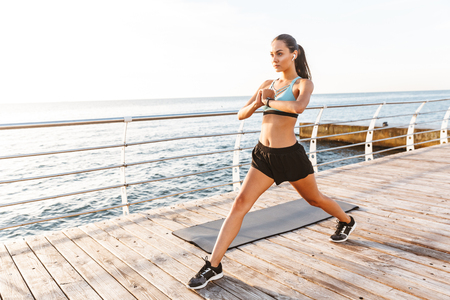 Image of energetic brunette sportswoman 20s in tracksuit doing sports and stretching body on boardwalk near seaside with wireless earbud