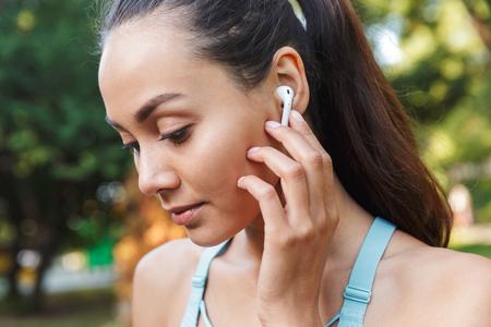 Primer plano de la imagen de una hermosa mujer caucásica de 20 años en ropa deportiva con auriculares inalámbricos y escuchando música durante la caminata en el parque verde