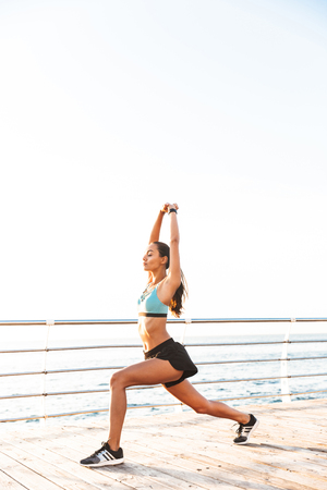 Image of energetic yoga woman 20s in tracksuit squatting and raising arms during sports training on boardwalk at seaside