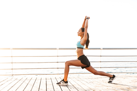 Profile photo of energetic brunette sportswoman 20s in tracksuit stretching legs and raising arms during workout on boardwalk at seaside