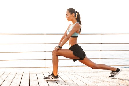 Profile photo of energetic brunette sportswoman 20s in tracksuit doing lunges and stretching legs on boardwalk at seaside Stock Photo