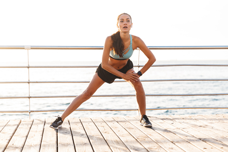 Photo of energetic brunette sportswoman 20s in tracksuit stretching legs and doing side lunges during workout on boardwalk at seaside Stock Photo