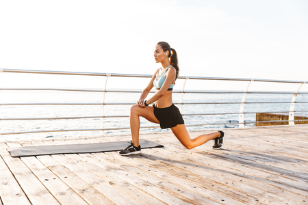 Profile photo of energetic brunette sportswoman 20s in tracksuit doing lunges and stretching legs on boardwalk near seaside