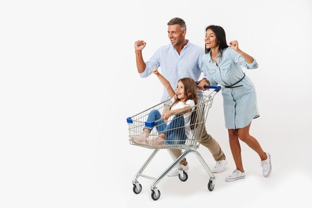 Excited family runnnig while shopping together with a supermarket trolley, little daughter sitting in a trolley isolated