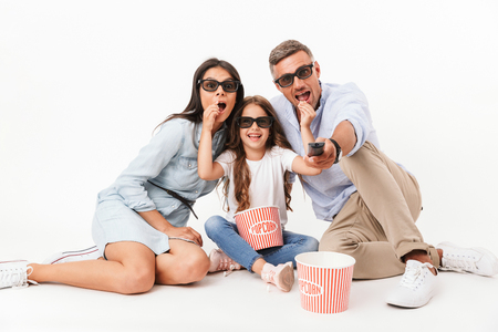 Portrait of a joyful family father, mother, little daughter in 3D glasses eating popcorn and watching TV while sitting isolated over gray background