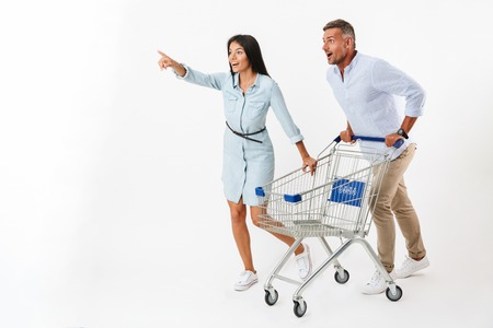 Happy couple running with a shopping cart at the supermarket and pointing away isolated Stockfoto