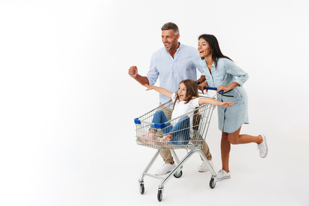 Happy family runnnig tout en faisant du shopping avec un chariot de supermarché, petite fille assise dans un chariot isolé