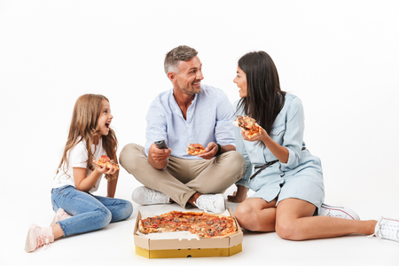 Portrait of a joyful family father, mother, little daughter having fun while eating pizza and watching TV isolated over gray background Stockfoto