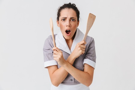 Portrait of a shocked young housemaid dressed in uniform holding spade and a spoon isolated over white background Zdjęcie Seryjne