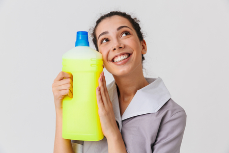 Portrait of a satisfied young housemaid dressed in uniform holding detergent isolated over white background Stock Photo