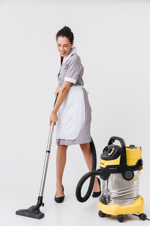Full length of a cheerful young housemaid dressed in uniform using vacuum cleaner isolated over white background