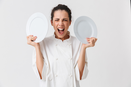 Portrait of a furious young woman cook dressed in uniform showing two plates isolated over white background