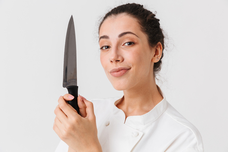 Portrait of a pensive young woman cook dressed in uniform holding kitchen knife and looking at camera isolated over white background Standard-Bild
