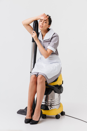 Full length of a tired young housemaid dressed in uniform sitting on a vacuum cleaner isolated over white background Zdjęcie Seryjne