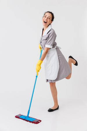 Full length portrait of a joyful young housemaid dressed in uniform using a mop isolated over white background Stock Photo