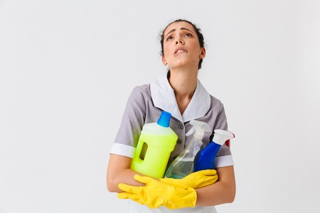 Portrait of an exhausted young housemaid dressed in uniform and rubber gloves holding detergents isolated over white background
